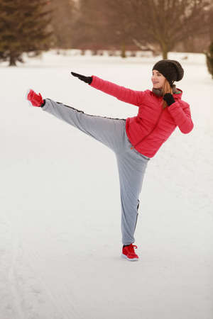 Outdoor sport exercising, sporty outfit ideas. Woman wearing warm sportswear training karate outside during winter.