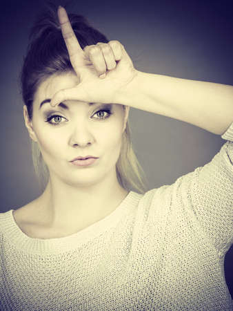 Woman showing mean sign, lame or loser gesture with L fingers on forehead, grey background. Stock Photo