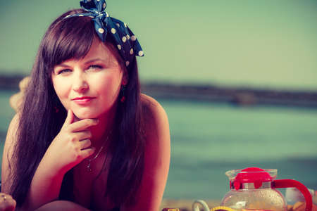 Brunette pin up woman with dotted bow in hair lying on beach, sea water in background