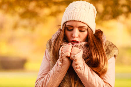 Woman wearing warm fashionable outfit walking in park during golden autumn weather feeling cold trying to warm herself up.