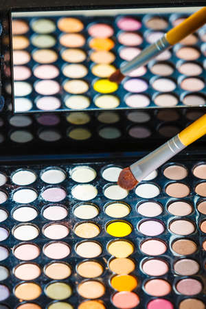 Cosmetic beauty procedures and makeover concept. Makeup professional eye shadows palette and brush. Make up applying.