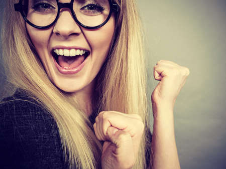 Closeup of weirdo woman face wearing big nerd geek eyeglasses having happy face expression, success or finding problem solution.