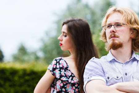 Offended upset couple young male and female not talking to each other sitting back to back after argument quarrel. Disagreement in relationship. Stock Photo