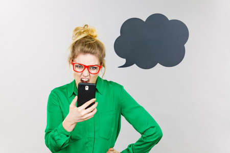 mobbing: Angry business woman wearing green shirt and red eyeglasses looking at phone with black thinking or speech bubble next to her.