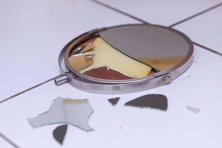 Destruction, low self esteem, accident, conflict concept. Broken mirror lying on tiled floor