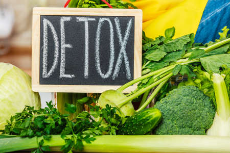 Many green vegetables in kitchen and board with detox sign. Healthy eating concept.