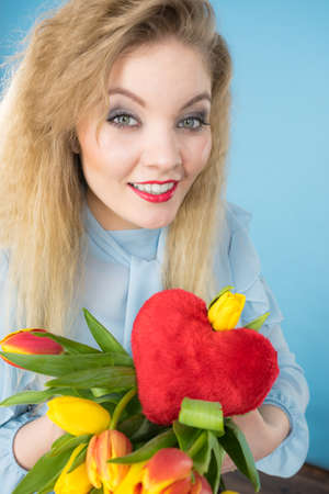 International womens or valentines day. Attractive happy woman blonde hair fashion make up holding tulips bunch and red heart sign. On blue Stock Photo