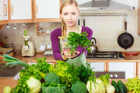 Buying healthy dieting food concept. Woman in kitchen having many green vegetables holding small shopping basket trolley with parsley inside.