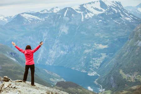 Tourism vacation and travel. Happy free tourist woman with arms raised outstretched up looking at Geirangerfjord and mountains landscape from Dalsnibba viewpoint, Norway Scandinavia. Stock Photo