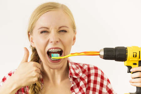 Funny teenage woman wearing braces holding drill about to brush her teeth.