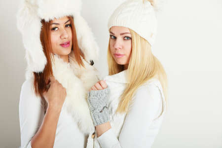 Clothing people fashion concept. Two ladies in winter outfit. Blonde woman together with mulatto girl, wearing white warm clothes.
