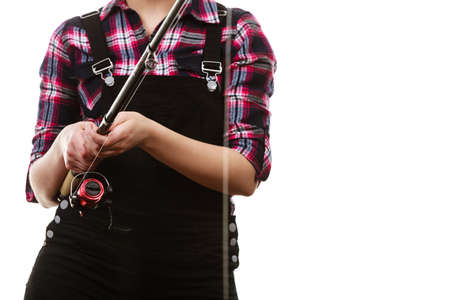 dungarees: Spinning equipment, angling, fisherwoman, sport for woman concept. Woman hand holding fishing rod