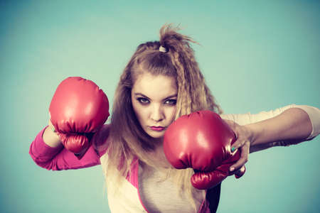 Cute blonde girl female boxer with big fun red gloves playing sports boxing studio shot on blue