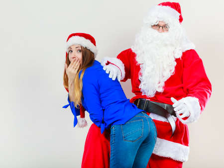 Christmas holiday concept. Man wearing Santa Claus costume spanking woman in christmassy hat.