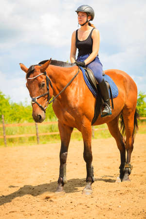 Taking care of animals, horsemanship, western competitions concept. Jockey girl doing horse riding on countryside meadow, sunny day outside Stock Photo