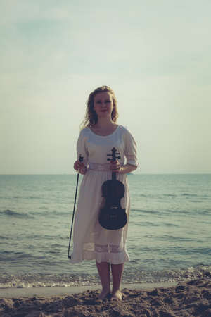 Music love, hobby and everyday passion concept. Woman on beach near sea holding violin