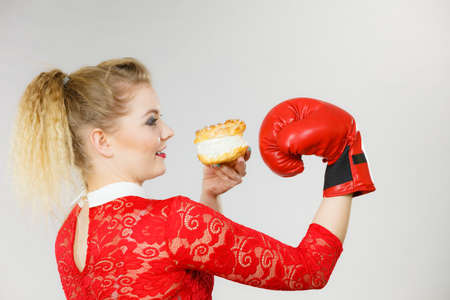 Positive woman fighting with her bad habits, being on diet. Female wearing boxing glove holding sweet dessert, cream cupcake.