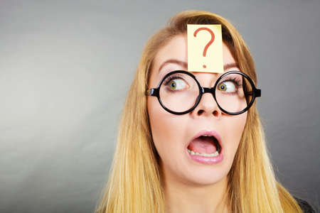Crazy wondering face expression concept. Wierdo nerd woman having question mark on forehead and geek eyeglasses. Stock Photo