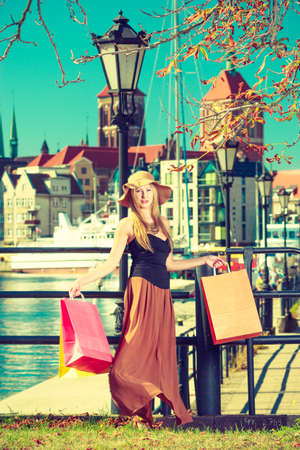Spending money on sales, buying things concept. Fashionable woman relaxing and standing with shopping bags in town, wearing glamorous outfit and big sun hat Stok Fotoğraf