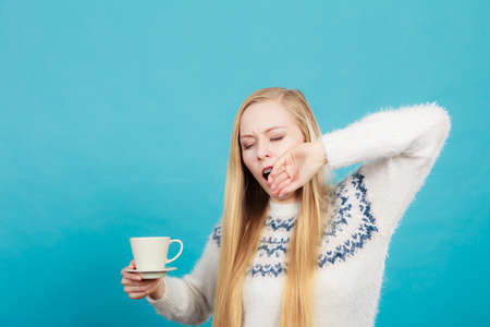 Addiction and caffeine need concept. Sleepy yawning blonde woman holding cup of coffee about to drink it. Stock Photo