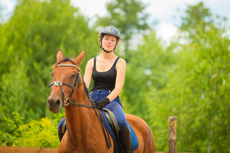 Taking care of animals, horsemanship, western competitions concept. Jockey girl doing horse riding on countryside meadow, sunny day outside Stock fotó