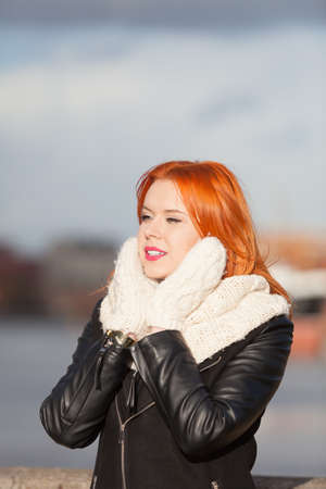 Winter fashion. Beauty girl portrait red hair young woman in warm clothing outdoor enjoying sunlight on sunny day. Stock Photo