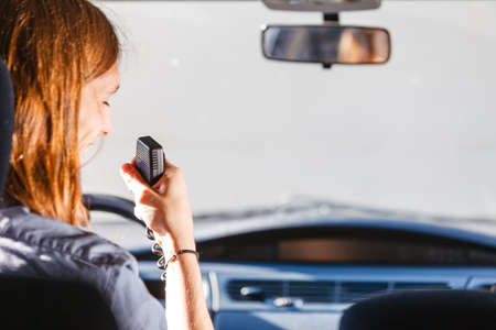Talking while drive, auto walkie talkie, comunication concept. Young man driving car using cb radio