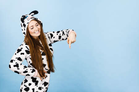 Happy teenage girl in funny nightclothes, pajamas cartoon style pointing down at copy space with positive face expression, studio shot on blue. Advertisement concept