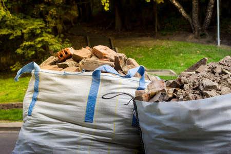 생산 또는 혁신으로부터의 낭비. 잔해와 함께 두 개의 큰 가방 컨테이너입니다. 스톡 콘텐츠