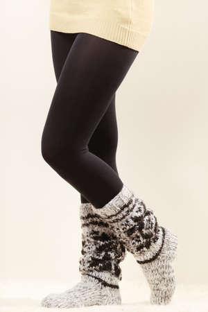 Winter mode. De benen van de vrouw die modieuze wintertijd dragen, wollen warme sokken en zwarte legging