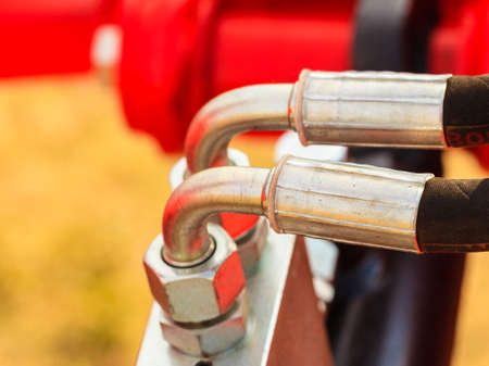 Industrial detailed pneumatic, hydraulic machinery concept. Pump made of steel on red machine closeup. Stock Photo
