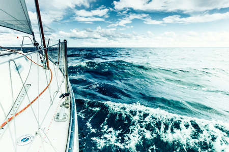 Yachting on sail boat bow stern shot splashing sea water. Sporty transportation conept. Stock Photo