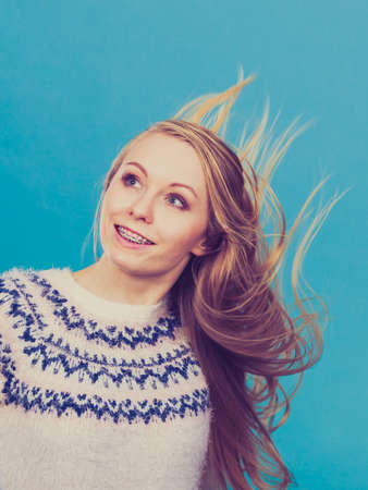 Hairstyles ideas, happiness concept. Crazy teenage woman wearing winter jumper with windblown blonde hair