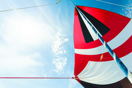 spinnaker: Spinnaker with uphaul on sail boat, blue sky in background. Marine sailing objects concept.