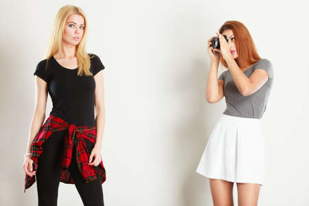 Photographer and model. Mulatto girl shooting images, taking photos with camera, photographing blonde woman Stock Photo