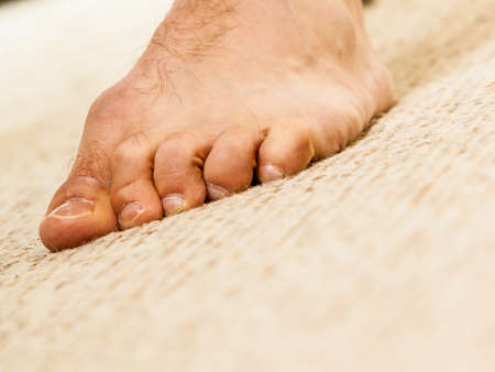 Orthopaedist, human body, feet care concept. Closeup of man foot standing on carpet