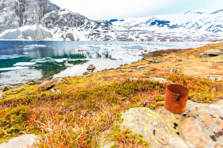 Polluted nature. Old rusty can abandoned on lake shore, beautiful mountains area in the background. Earth ecology