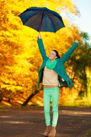 Autumnal fashion concept. Woman walking in park during golden autumn weather, enjoying nature holding umbrella having fun.