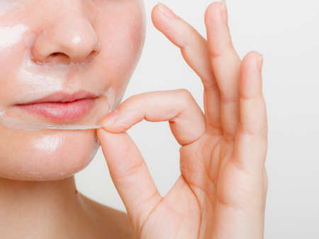 Beauty skin care cosmetics and health concept. Young woman face, girl removing facial peel off mask. Peeling.