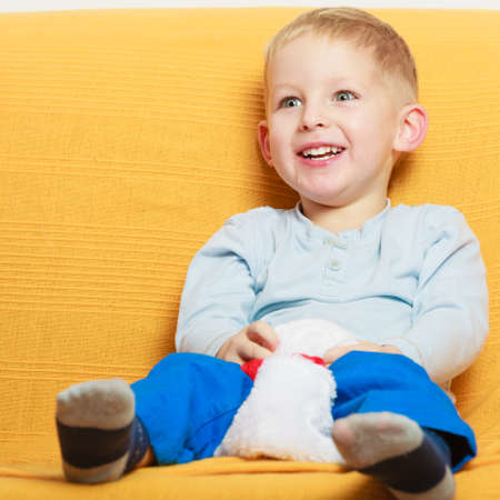 Childhood, kids imagination concept. Little young boy playing on sofa and having fun