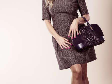 Mode kleding mensen concept. Chique vrouw met zwarte, lederen handtas. Vrouw draagt ??elegante jurk.