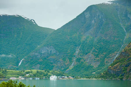 Tourism vacation and travel. Mountains landscape and big cruise ship on fjord Sognefjord in Flam Norway Scandinavia. Stock Photo