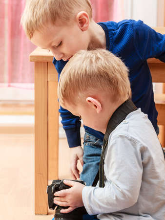 Technology and childhood. Discovering and fun. Children play and take photo in home. Boys hold camera look at screen. Stock Photo
