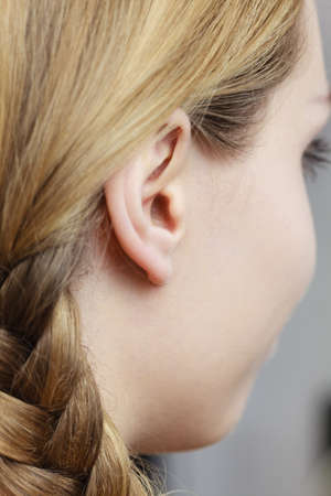 Detail of the head with female human ear and blonde braid hair, close up