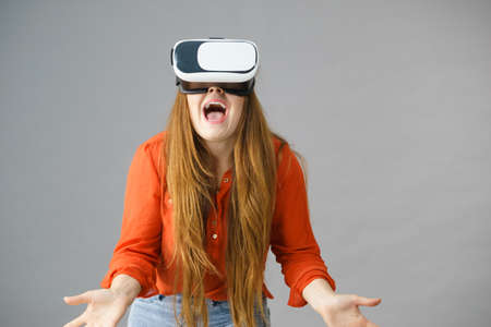 Young emotional woman wearing virtual reality goggles headset, vr box.