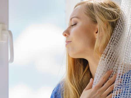 Mujer feliz con el pelo largo y rubio sentado en el alféizar de la ventana y relajarse, meditar o pensar sosteniendo la cortina de encaje blanco.