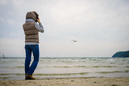 Relaxation and leisure. Woman walking on beach. Female tourist relax near to water place on nature. Autumn cold season.