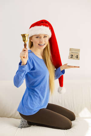 4c57c3f74b Happy positive young teenage woman wearing Santa Claus christmas hat  holding calendar with 24 december date