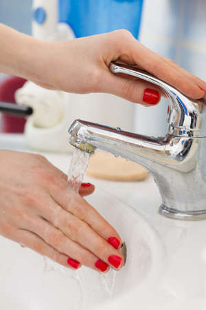 Woman cleaning washing hands under flowing tap water in the bathroom. Female hands with red nails manicure. Hygiene, skin treatment concept. Stock Photo