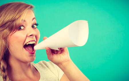Communication concept. Young blonde woman talking loud through megaphone made of paper.